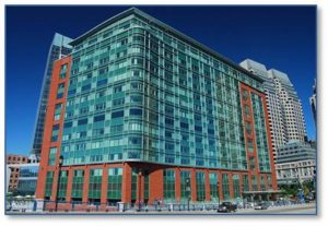 To take advantage of this new modern waterfront, the firms of Modern Continental Enterprises and the architectural firm of Bergmeyer Associates Inc. renamed and renovated the structure. They turned an abandoned warehouse into 370,000 square feet of commercial real estate space. Brick and green-glass curtain wall replaces the old exterior skin on the two waterfront-facing sides of the building, while masonry dominates the landward sides. This design, which includes wavelike curves, unites the city with the water.