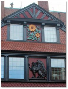 A large wooden carving of a sunflower painted in bright yellow and green hangs under the eave above the front door.  Beneath it, in the center of a windowed gallery you see a carving of a black gryphon.