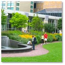 "People put blankets on the lawn and have a picnic while listening to music. They eat lunch at the café tables or just read a book while enjoying the beautiful plantings. They stroll through the Pru Garden and listen to the purling of the ""water feature."""