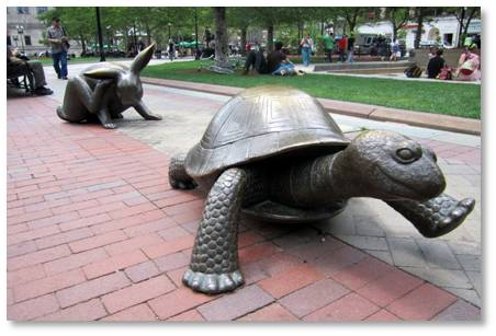 "The Tortoise and the Hare are large bronze critters that can be found on the bricks in front of the fountain. They were created by local sculptor Nancy Schön. A runner herself, she wanted to create a statue to honor those who run the marathon but knew it was impossible to create one human who could encompass the two genders and myriad nationalities who participated. Instead, she looked to create ""a meaningful metaphor for the race."" She also wanted a sculpture that would be kid-friendly."