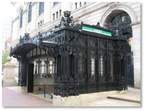 Many Bostonians are familiar with the beautiful Art Nouveau Metro stations of Paris yet they walk right past our city's own Beaux-Arts masterpiece. The T's Green Line inbound Copley Station headhouse is one of a kind and unmatched by any other station. Made of ornamental wrought iron, it was designed by the firm of Fox, Jenny and Gale to match and enhance the elegance of the Boston Public Library building behind it. The ironwork echoes the library's graceful Italianate lanterns, and the canopy arch over the stairway to the inbound platform includes a seal with an open book.