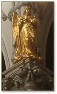 Four gilded angels peer down from the main pillars at the intersection of the nave and transept in front of the chancel, or where the two parts of the cross-shaped floorplan meet. Wings outstretched and hands folded in prayer, they have identical designs and stand on frothy gilded clouds.