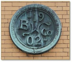 "The Boston Wharf Company's staff architects designed ranks of warehouses between the 1880s and the 1920s in uniform heights and sizes. The buildings are constructed of masonry with ""classically inspired details concentrated at the entrances and cornices,"" and flat roofs. A circular copper medallion stamps each of the buildings with a BWC logo in relief."