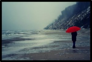 woman on beach, rain, umbrella, loneliness